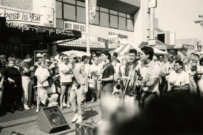 Black and white picture of band performing in the middle of the street