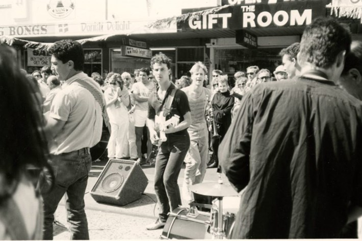 Black and white picture of a man playing guitar to people passing by