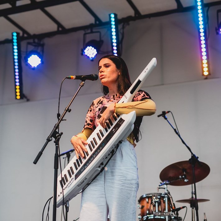 Performer sings and plays keyboard guitar on stage