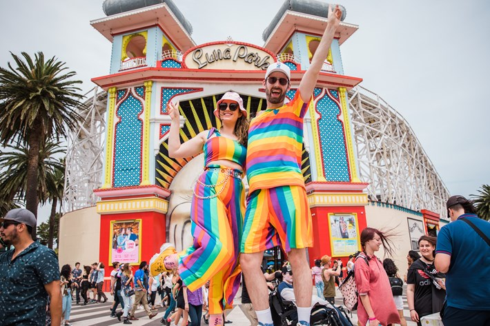 Two people in matching rainbow outfits strike a post in front of Luna Park